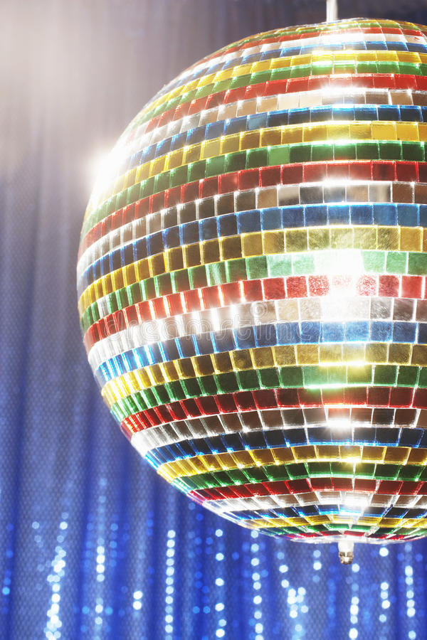 Bola de discoteca multicolora delante de la cortina azul de la etapa cosechada imagen de archivo libre de regalías