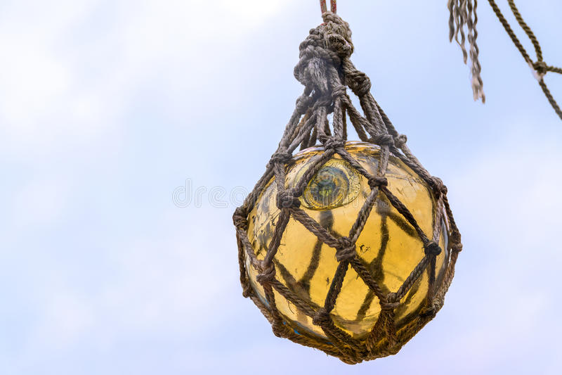Bola de flutuador de vidro amarela histórica da pesca que pendura em uma rede a d fotografia de stock royalty free