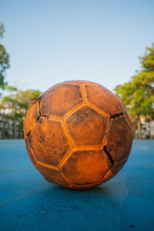 Bola de futebol amarela velha no campo de futebol azul fotos de stock royalty free