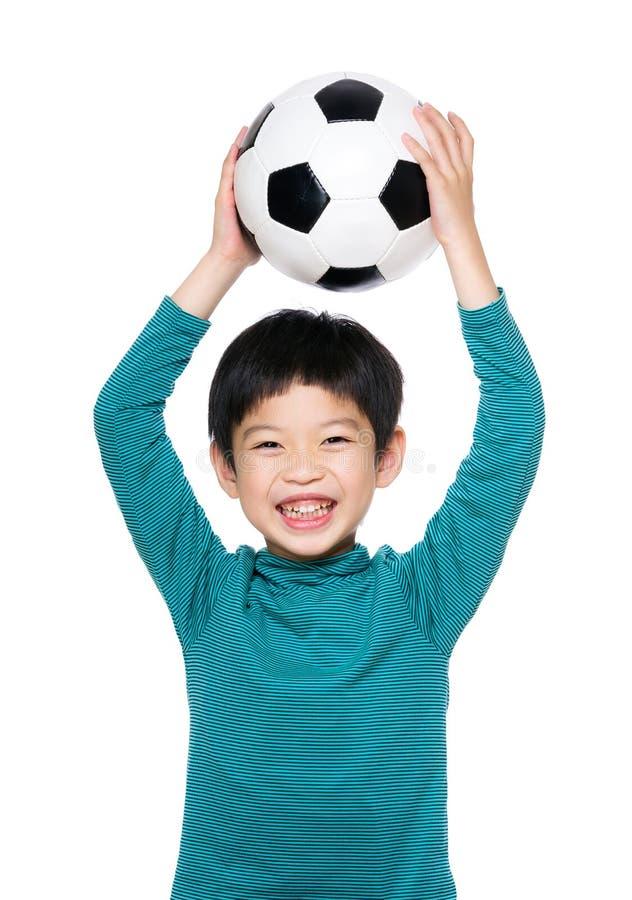 Bola de futebol asiática do aumento do rapaz pequeno acima imagem de stock royalty free