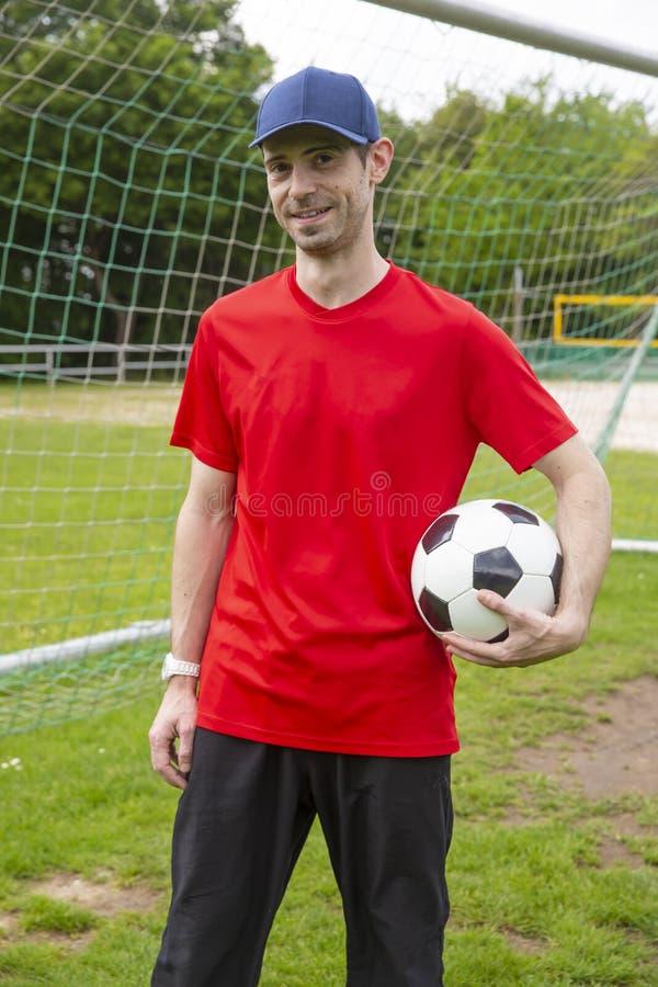 Bola de futebol da posse do goleiros fotografia de stock