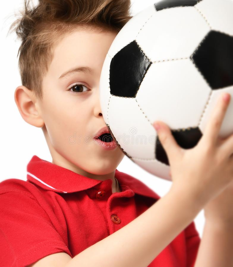 Bola de futebol da posse do jogador do menino do esporte do fã no t-shirt vermelho que comemora feliz surpreendido fotografia de stock royalty free