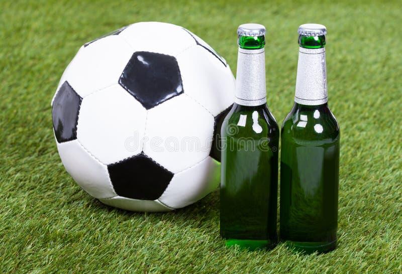 Bola de futebol e garrafas de cerveja na grama verde foto de stock
