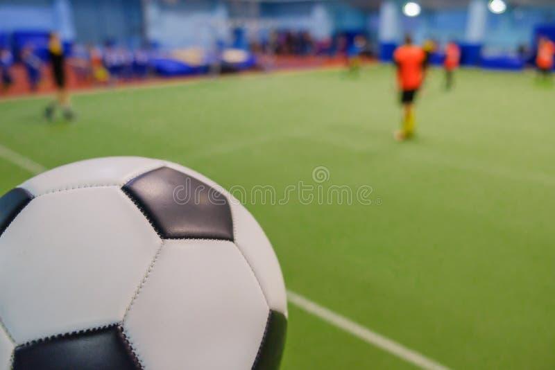Bola de futebol em estádio e em jogadores de futebol defocused no campo imagem de stock