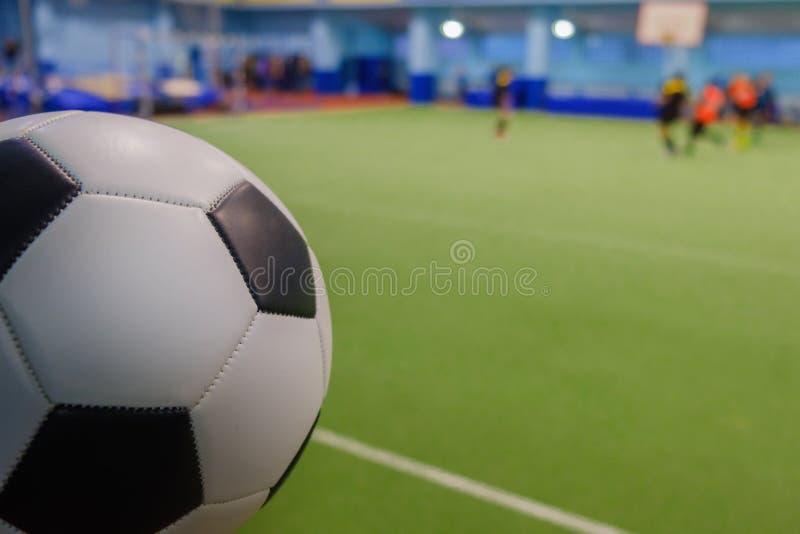 Bola de futebol em estádio e em jogadores de futebol defocused no campo imagens de stock royalty free