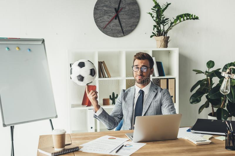 bola de futebol de giro do homem de negócios novo no dedo imagens de stock royalty free