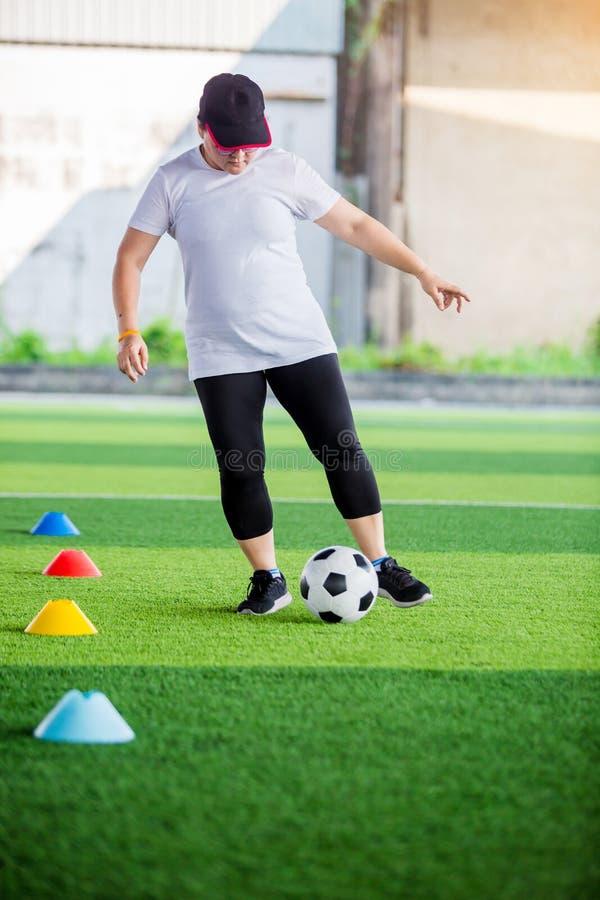 Bola de futebol movimentar-se e de controle do jogador de futebol da mulher entre marcadores do cone no relvado artificial imagens de stock