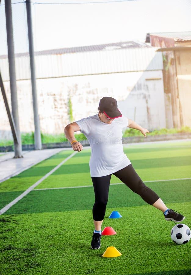 Bola de futebol movimentar-se e de controle do jogador de futebol da mulher entre marcadores do cone no relvado artificial fotografia de stock royalty free