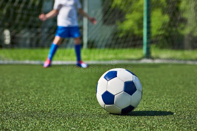 Bola de futebol na grama e no menino do futebol no depositário de porta fotos de stock royalty free