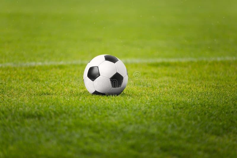 A bola de futebol no campo do verde do estádio O futebol lança dentro o fundo foto de stock royalty free