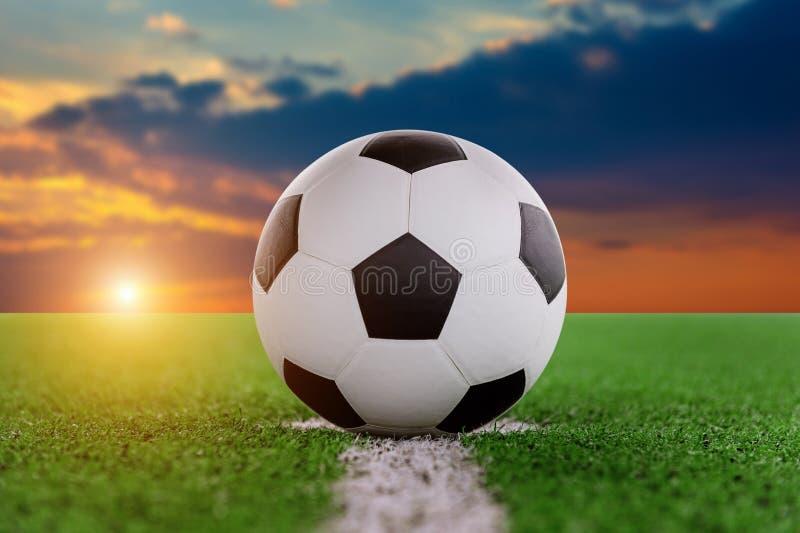 Bola de futebol no campo de futebol no por do sol fotografia de stock royalty free
