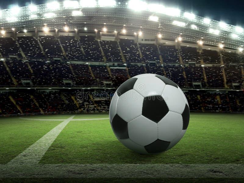 A bola de futebol no estádio verde, arena na noite iluminou projetores brilhantes fotografia de stock royalty free