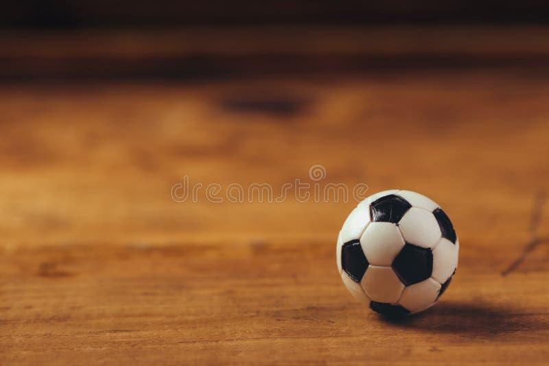 Bola de futebol plástica diminuta na tabela de madeira fotografia de stock