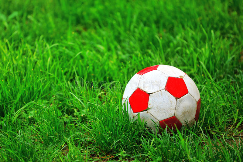 Bola de futebol velha na grama foto de stock