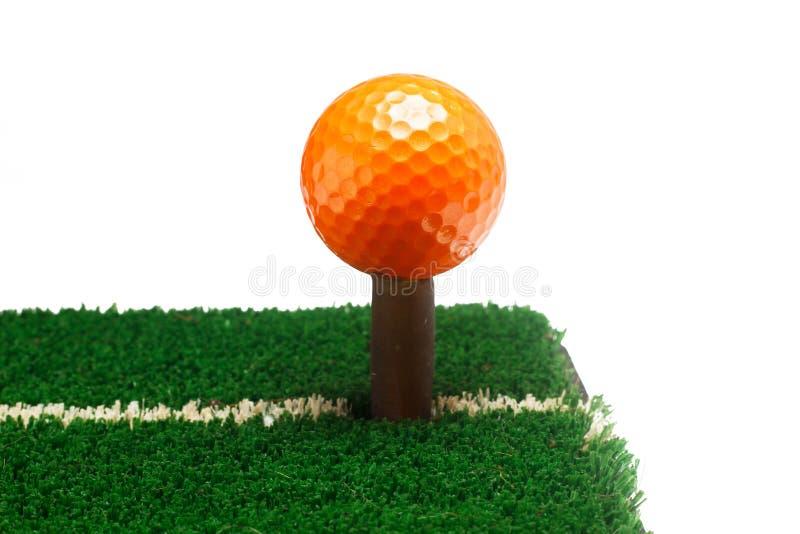 Bola de golfe alaranjada na grama verde, foco seletivo imagens de stock