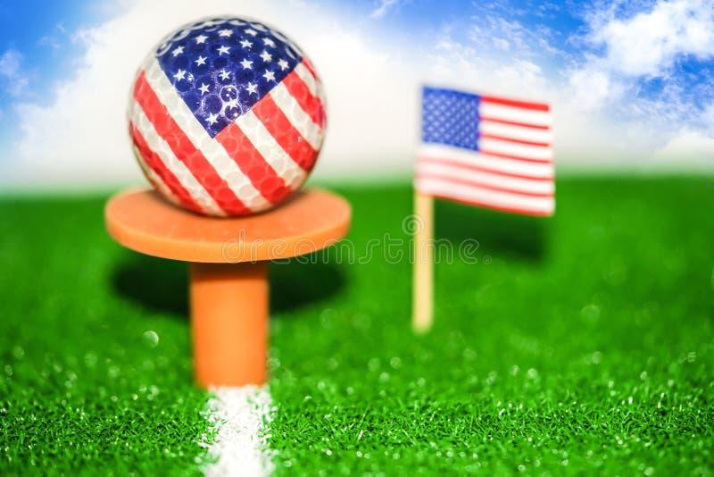 Bola de golfe com a bandeira dos EUA no gramado ou no campo verde foto de stock