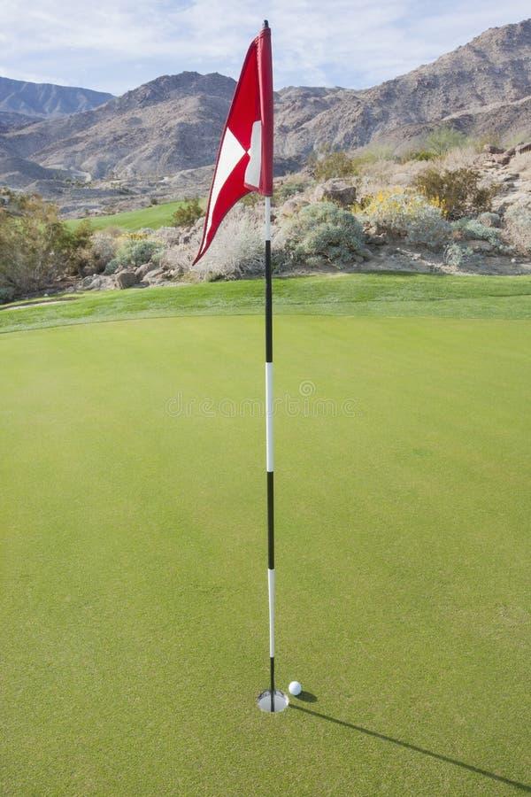 Bola de golfe e bandeira no curso fotos de stock royalty free