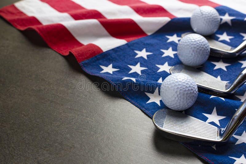 Bola de golfe e clube de golfe com a bandeira dos EUA no fundo preto de madeira da tabela imagem de stock