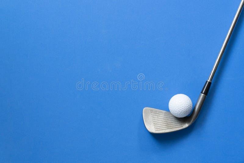 Bola de golfe e clube de golfe no fundo azul fotos de stock
