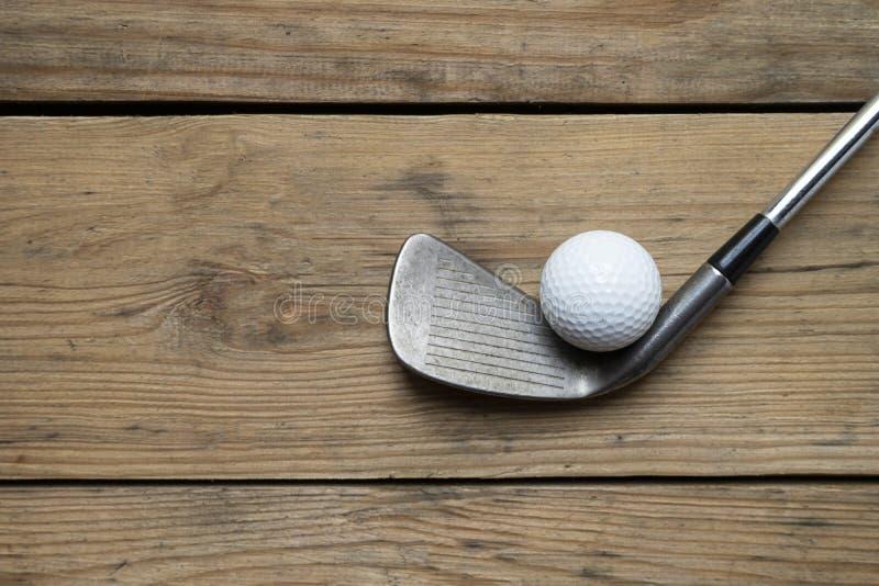 Bola de golfe e clube de golfe no fundo de madeira da tabela imagens de stock royalty free