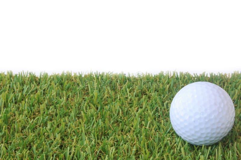 Bola de golfe isolada na grama verde sobre o fundo branco imagens de stock