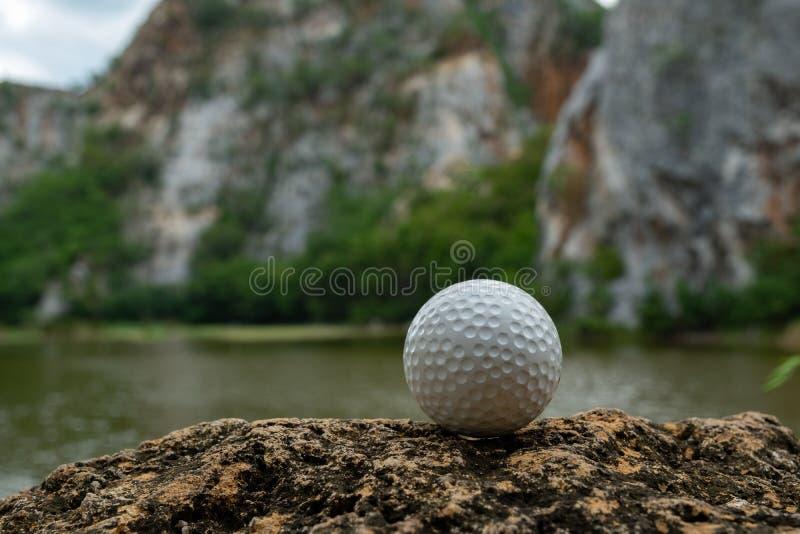 Bola de golfe na grama perto do lago pequeno imagem de stock royalty free