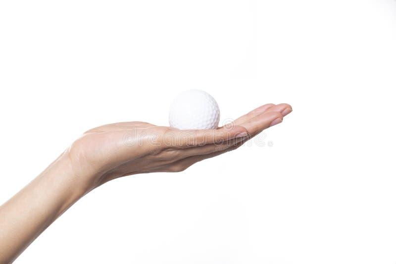 Bola de golfe na mão da mulher imagem de stock royalty free
