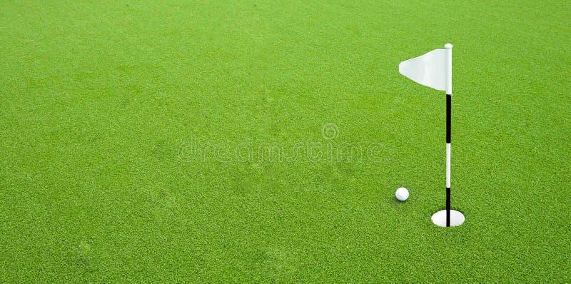 Bola de golfe perto do furo fotos de stock