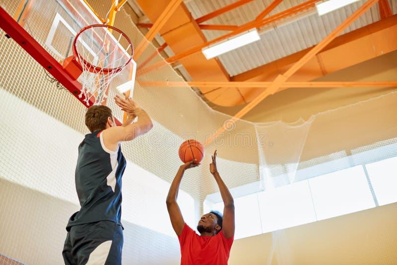 Bola de jogo do jogador desportivo na cesta fotos de stock royalty free