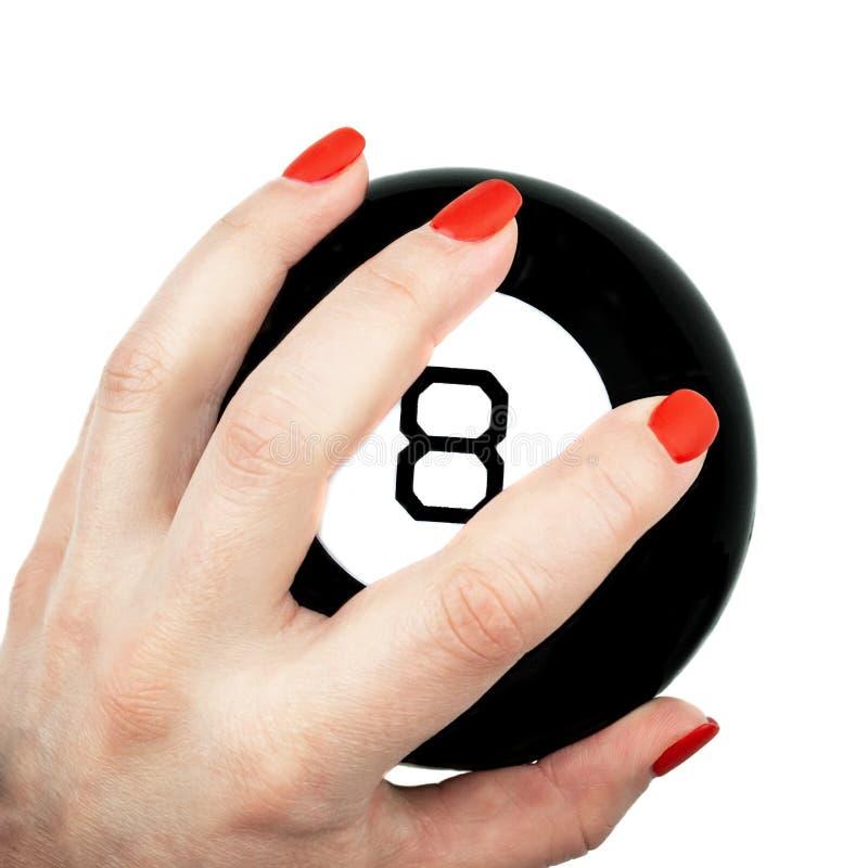 Bola de la magia 8 de predicciones en la mano femenina aislada en el fondo blanco foto de archivo
