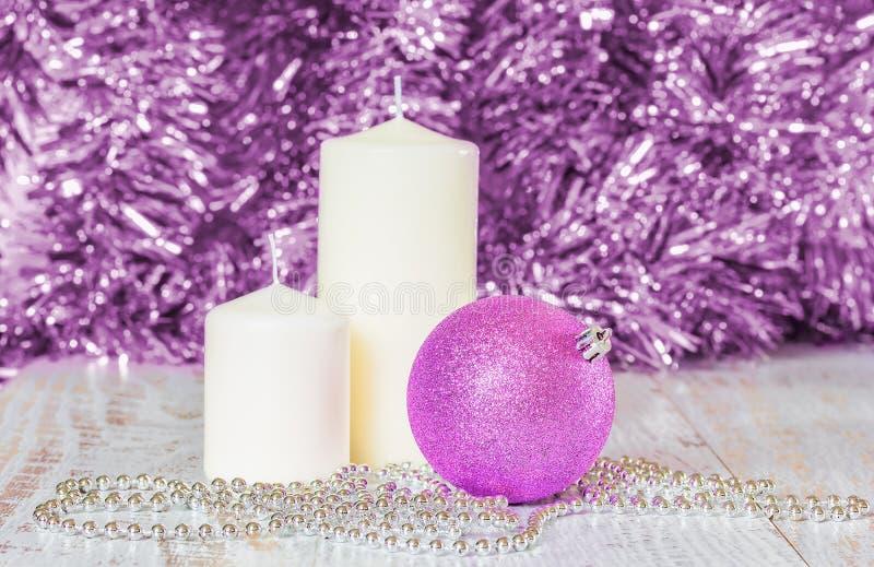 Bola de la Navidad de la lila, dos velas blancas y gotas de plata fotos de archivo