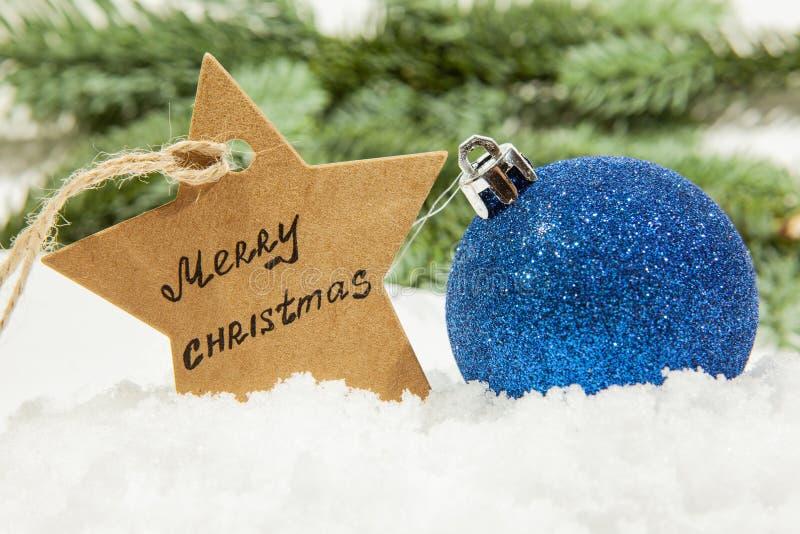 Bola de la Navidad en azul en la nieve blanca y una estrella con la Feliz Navidad de la inscripción, en las ramas del abeto del f fotos de archivo libres de regalías