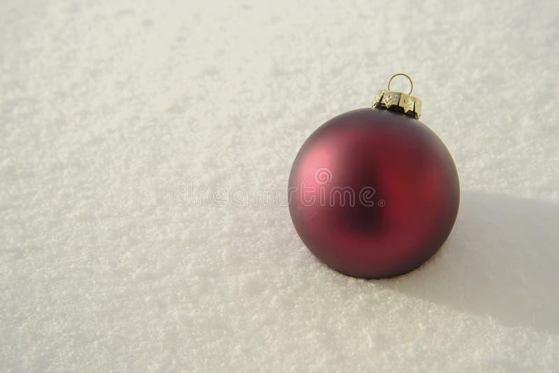 Bola de la Navidad en nieve imagen de archivo