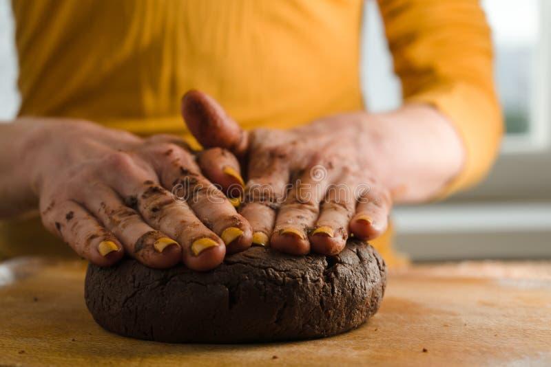 Bola de la pasta y del cacao presionados a un tablero de madera con sus manos imagenes de archivo