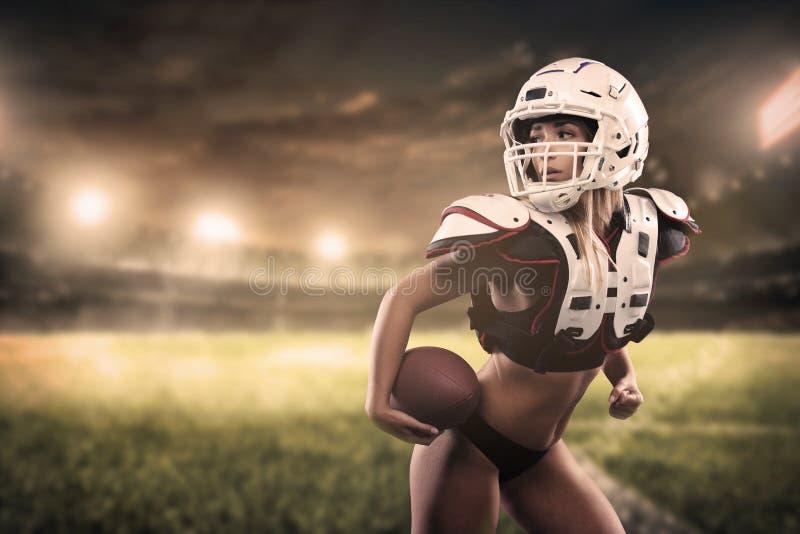 Bola de la tenencia del jugador de la mujer del fútbol americano en la opinión del panorama del estadio foto de archivo libre de regalías