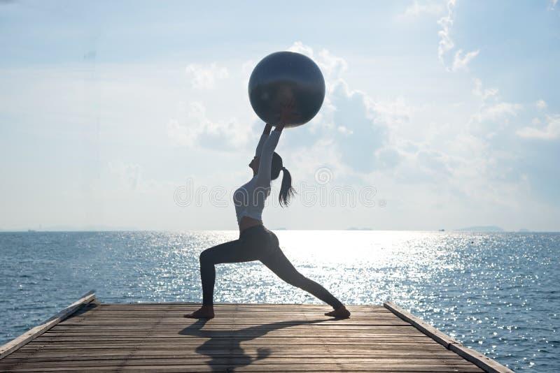 Bola de la yoga, mujer joven de la bola de los pilates foto de archivo