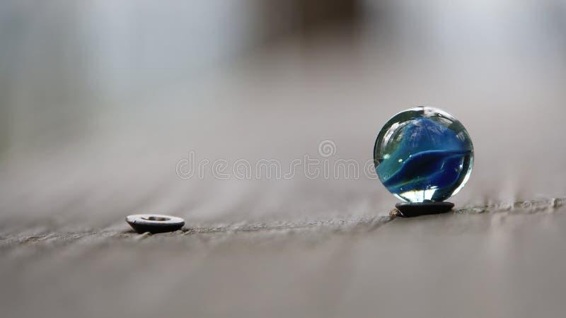 Bola de mármore azul que está na cabeça do parafuso imagens de stock
