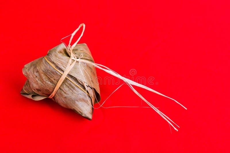 Bola de masa hervida o zongzi china fresca del arroz contra fondo rojo foto de archivo libre de regalías