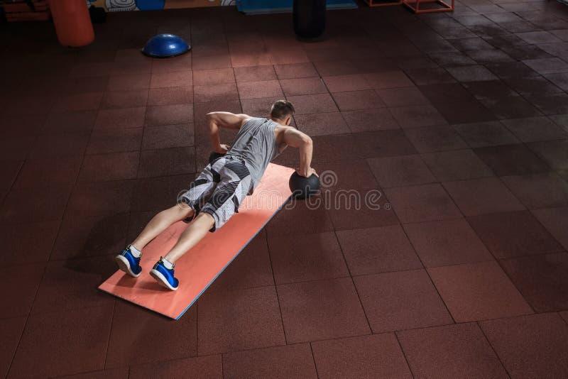 Bola de medicina masculina atrativa de Performing Push-Ups On do atleta foto de stock