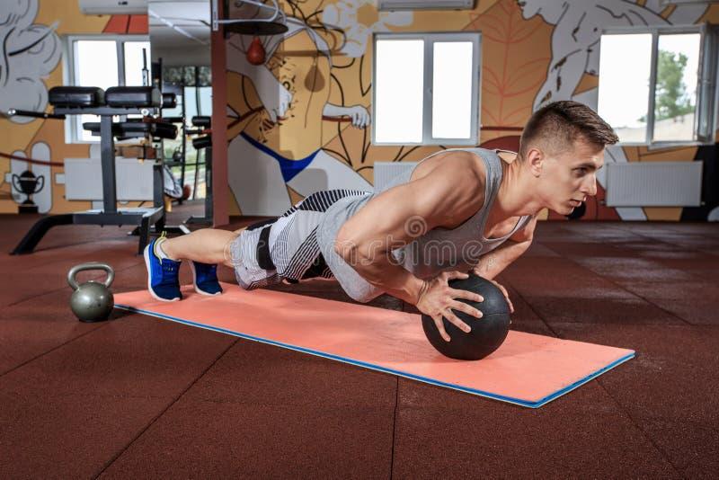 Bola de medicina masculina atrativa de Performing Push-Ups On do atleta fotografia de stock royalty free