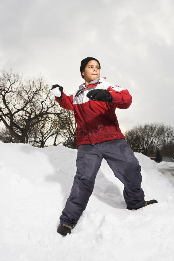Bola de nieve que lanza del muchacho. imagen de archivo