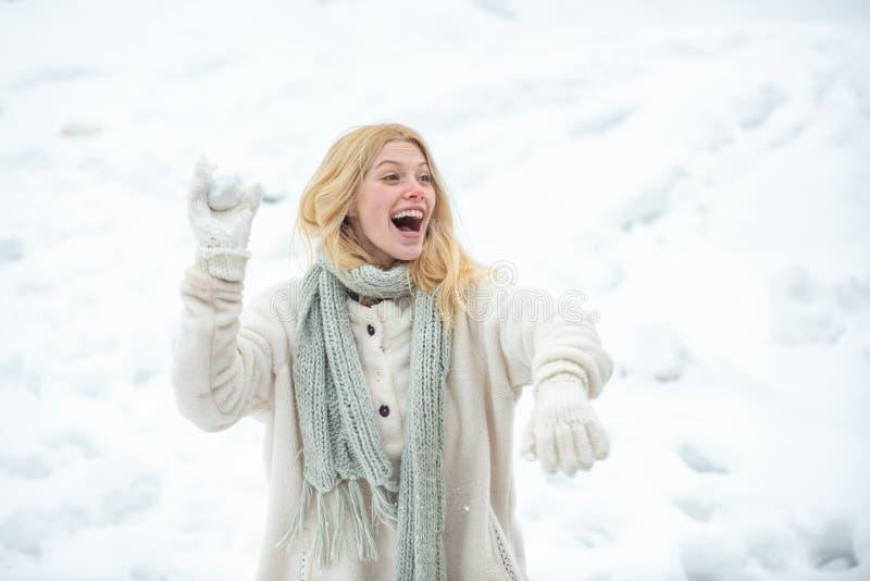 Bola de nieve que lanza de la mujer americana joven en el día soleado en el parque del invierno Muchacha que juega con nieve en p imágenes de archivo libres de regalías