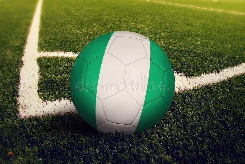 Bola de Nigeria en la posici?n del retroceso de la esquina, fondo del campo de f?tbol Tema nacional del f?tbol en hierba verde imagen de archivo libre de regalías