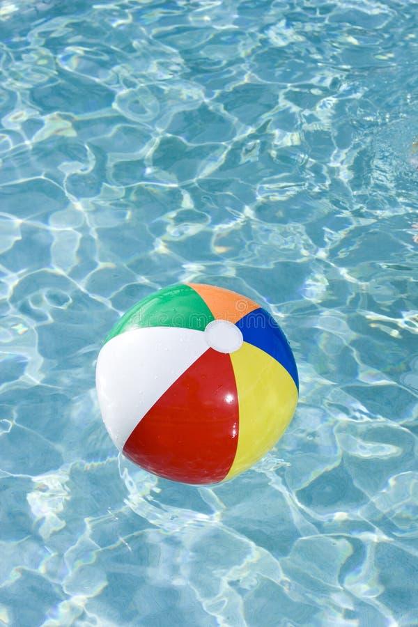 Bola de playa colorida que flota en piscina imágenes de archivo libres de regalías