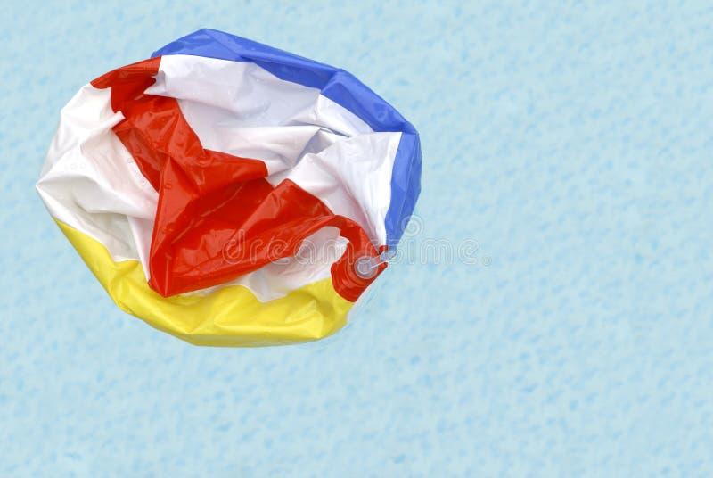 Bola de playa desinflada en piscina fotografía de archivo