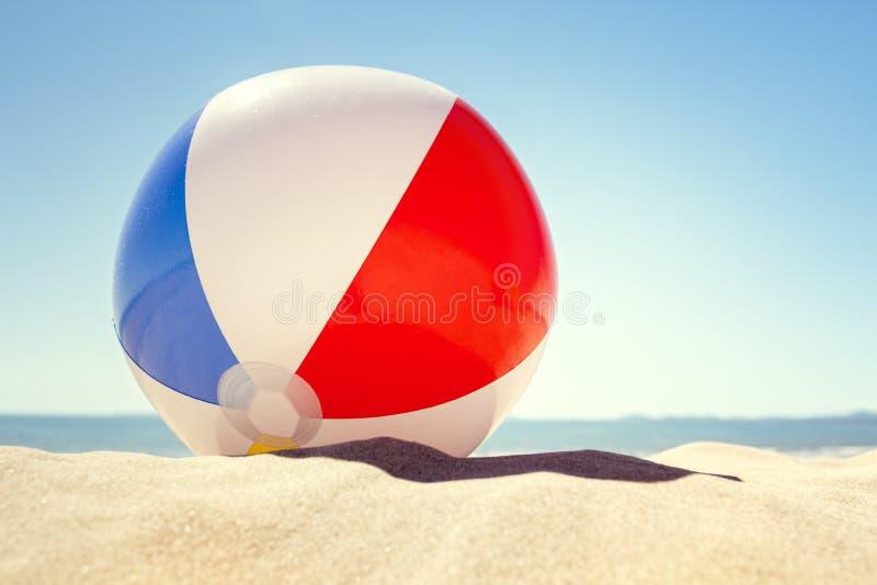 Bola de praia na areia fotografia de stock