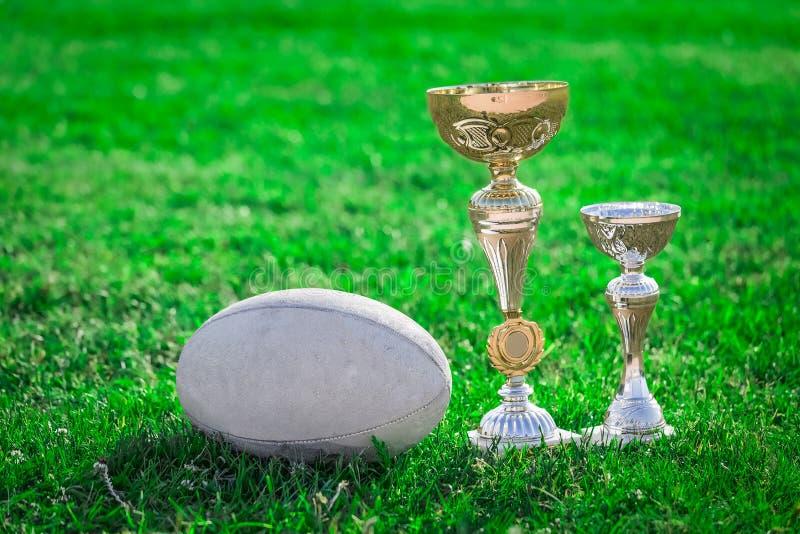 Bola de rugby e troféus do rugby na grama fotos de stock