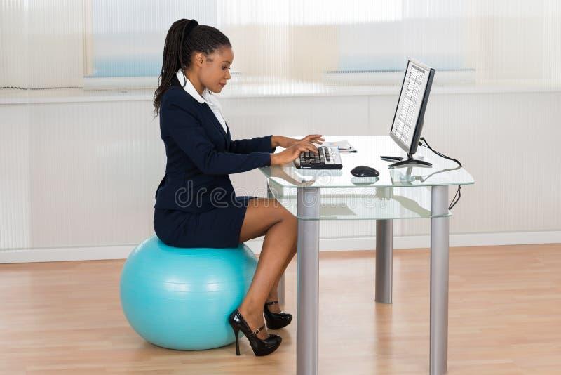 Bola de Sitting On Fitness da mulher de negócios usando o computador foto de stock