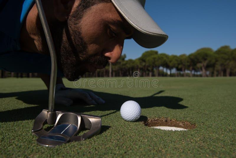 Bola de sopro do jogador de golfe no furo imagens de stock