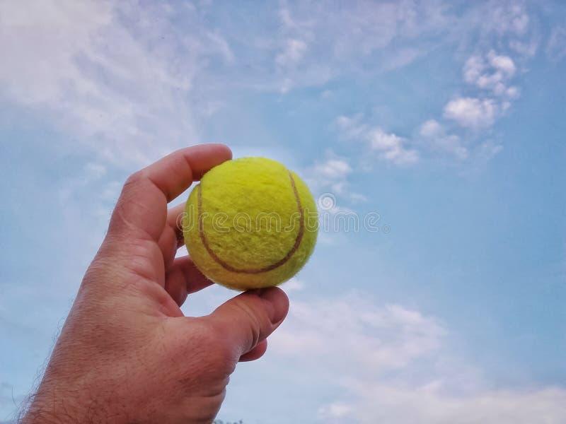 Bola de tênis à disposição contra o céu azul foto de stock royalty free